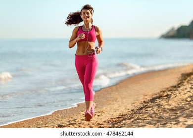 Fitness runner woman running on beach  Sporty athlete training cardio barefoot with determination under summer sun. She leads a healthy lifestyle.