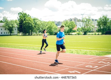 Fitness running couple jogging on athletics stadium track open air during hot summer day. Competition concept. Support. Toned image.