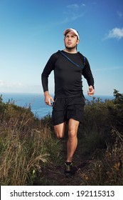fitness running man on mountain trail near ocean exercising for marathon training