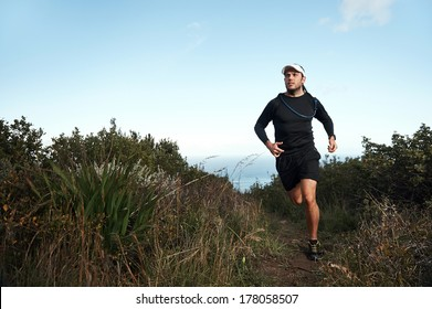 fitness running man on mountainn trail near ocean exercising for marathon training