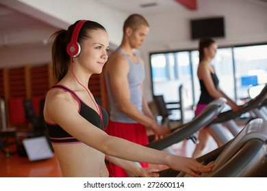 Fitness running people. Sports people running on the treadmill at the gym. Athletes wearing sportswear and running in the gym a rear.