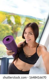 Fitness seflie woman taking photo at yoga class in gym studio. Asian girl smiling in activewear holding exercise mat vertical shot.
