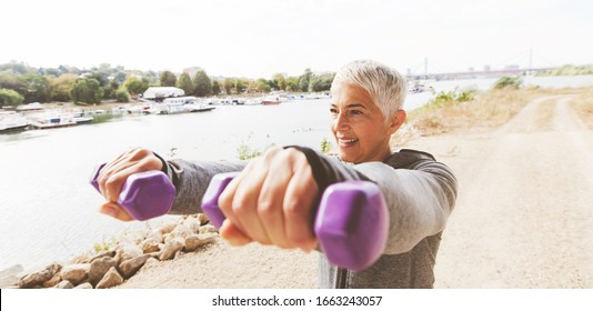 Fitness Senior Woman In Sports Clothes Working With Weights Outdoor .