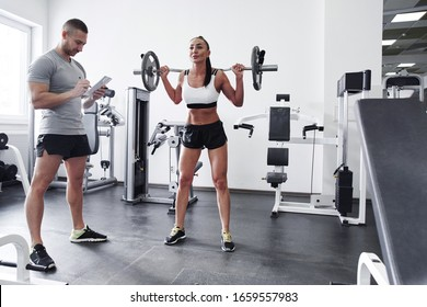 Fitness sexy brunette woman in top and shorts pumps muscles on sports equipment with trainer in gym, individual workout program