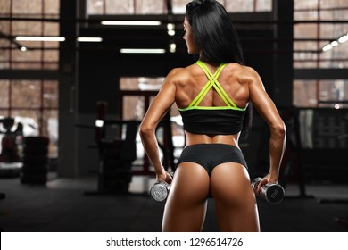 Fitness sexy woman working out in gym. Sexy beautiful butt in thong. Muscular girl, muscles back