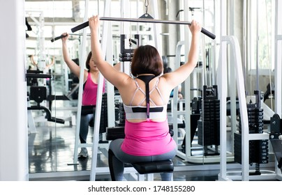 Fitness shoulder. Fit woman doing shoulder press exercise. Shoulder pull down machine. Fitness woman working out lat pulldown training at gym. Upper body strength exercise for the upper back.