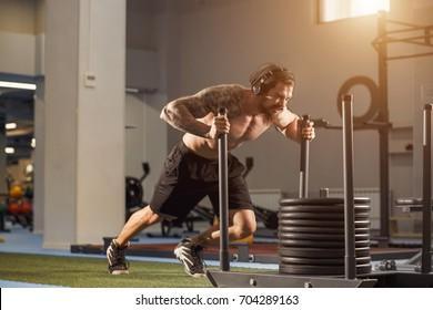 Fitness sled push man pushing weights workout exercise