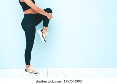 Fitness smiling black woman in sports clothing with afro curls hairstyle.She wearing sportswear.Young model stretching out legs before training.Female sitting in studio near blue wall. No face