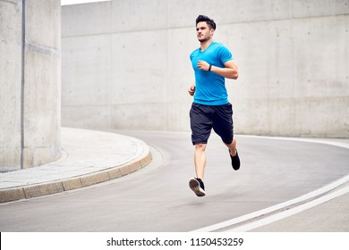Fitness and sport concept. Athletic man during jogging session in the city