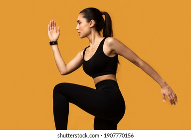 Fitness And Sport Concept. Side View Portrait Of Confident Fit Young Woman Wearing Activity Tracker Running, Lifting Leg Up, Exercising Isolated On Orange Background, Studio Shot. Energy And Workout