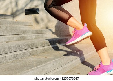 Fitness sport concept, woman in fashion sportswear doing fitness exercise in the city street over gray concrete background. Outdoor sports clothing and shoes, young woman running up the stairs.