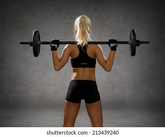 fitness, sport and dieting concept - sporty woman exercising with barbell from back over concrete wall background