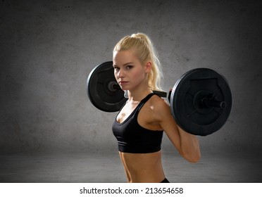 fitness, sport and dieting concept - sporty woman exercising with barbell over concrete wall background