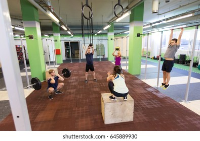 fitness, sport and exercising concept - group of people training with different equipment in gym