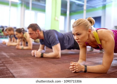 fitness, sport, exercising and people concept - woman with heart-rate tracker at group training doing plank exercise in gym