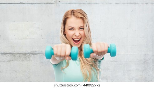 fitness, sport, exercising and people concept - smiling beautiful sporty woman with dumbbells over gray concrete wall background