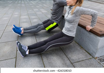 fitness, sport, exercising, training and people concept - couple doing triceps dip exercise on city street bench