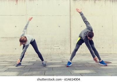 fitness, sport, exercising, training and people concept - couple stretching on city street