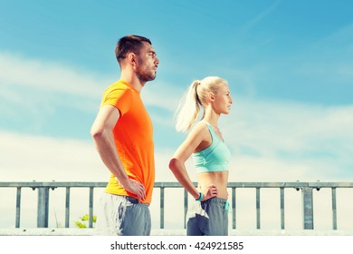 fitness, sport, friendship and healthy lifestyle concept - sporty couple outdoors