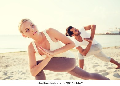 fitness, sport, friendship and lifestyle concept - close up of couple making yoga exercises on beach