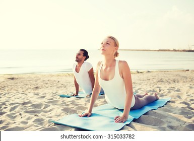 fitness, sport, friendship and lifestyle concept - couple making yoga exercises lying on mats outdoors