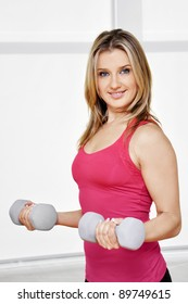Fitness sport girl smiling happy. Fitness woman lifting dumbbells