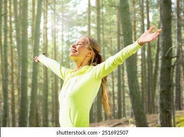 fitness, sport, happiness and people concept - happy woman raising hands over woods background