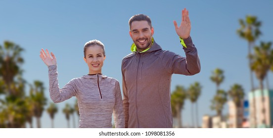 fitness, sport, and healthy lifestyle concept - smiling couple waving hand over venice beach background in california
