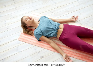 fitness, sport and healthy lifestyle concept - woman doing yoga corpse pose at studio