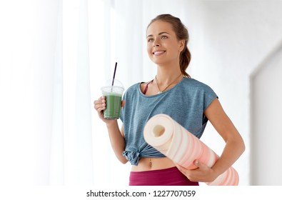 fitness, sport and healthy lifestyle concept - smiling young woman with cup of smoothie and exercise mat at yoga studio or gym