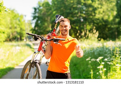 fitness, sport and healthy lifestyle concept - happy young man with bicycle outdoors in summer showing thumbs up