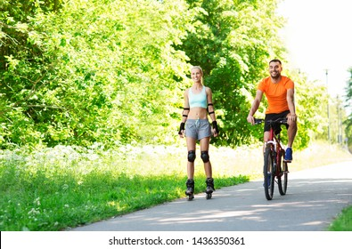 fitness, sport and healthy lifestyle concept - happy couple with rollerblades and bicycle riding in summer park