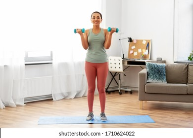 fitness, sport and healthy lifestyle concept - happy smiling young african american woman with dumbbells exercising at home