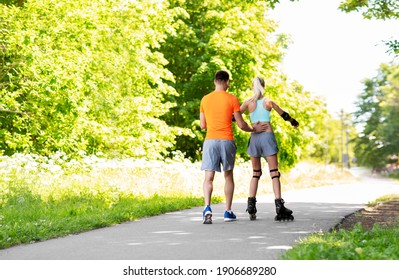 fitness, sport and healthy lifestyle concept - happy couple with roller skates riding outdoors
