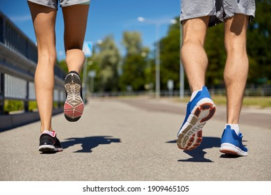 fitness, sport and healthy lifestyle concept - feet of sporty couple running along city road