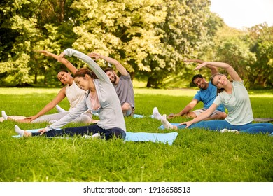 fitness, sport and healthy lifestyle concept - group of happy people exercising at summer park
