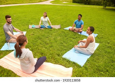 fitness, sport and healthy lifestyle concept - group of happy people sitting on yoga mats at park and talking