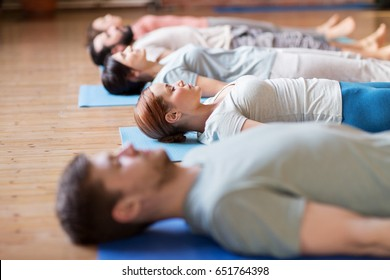 fitness, sport and healthy lifestyle concept - group of people making yoga exercises on mats at studio