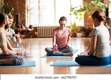 fitness, sport and healthy lifestyle concept - group of people with water bottles in yoga class resting on mats at studio