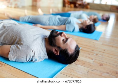 fitness, sport and healthy lifestyle concept - group of people doing yoga corpse pose on mats at studio