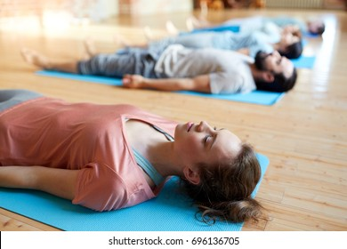 fitness, sport and healthy lifestyle concept - woman with group of people doing yoga corpse pose on mats at studio
