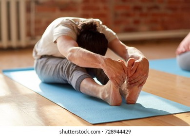 fitness, sport and healthy lifestyle concept - man doing yoga seated forward bend pose on mats at studio or gym
