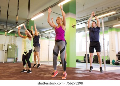 fitness, sport and healthy lifestyle concept - group of people exercising and jumping in gym