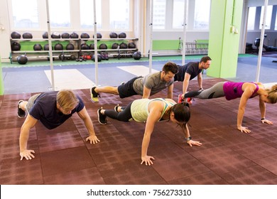 fitness, sport and healthy lifestyle concept - group of people doing push-ups in gym