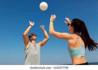 fitness, sport and lifestyle concept - happy couple with ball playing volleyball on summer beach