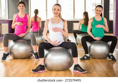 Fitness, sport and lifestyle concept - three pregnant women with exercise balls in gym.