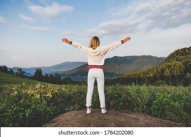 fitness, sport, peope and emotions concept - happy woman in sportswear enjoying freedom over mountains and blue sky background. rear view on the back
