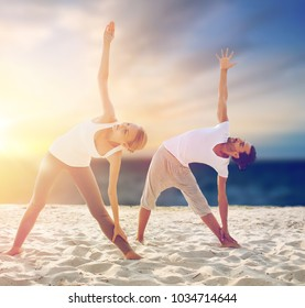 fitness, sport and people concept - couple making yoga exercises on beach