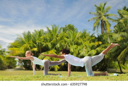 fitness, sport and people concept - couple making yoga balancing table pose outdoors over exotic natural background with palm trees