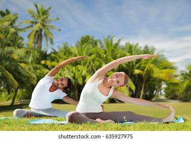 fitness, sport and people concept - couple making yoga exercises outdoors over exotic natural background with palm trees